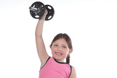 Strong and Healthy Girl. A little girl in sporty clothes lifts a weight over her head while smiling Royalty Free Stock Image