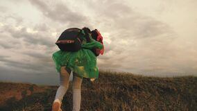 Strong and healthy girls travelers travel in colorful raincoats, climb mountain, hold hands, help each other. Free women