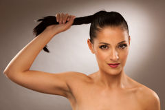 Strong healthy hair - Woman holds a pony tail over gray background Royalty Free Stock Photo