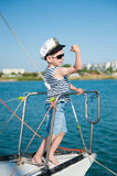 Strong and healthy kid captain showing muscles standing on board yacht stock image