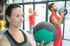 Strong healthy woman holding heavy medicine ball in gym workout. Strong healthy women holding heavy medicine ball in gym workout female Royalty Free Stock Images