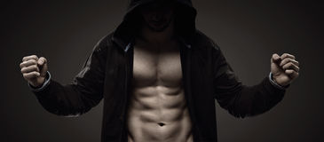 Strong hooded guy making muscles Royalty Free Stock Images