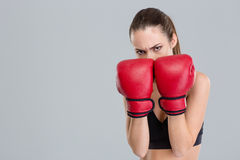 Strong intense fitness woman covered her face with boxing gloves Stock Photos
