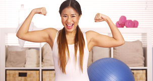 Strong Japanese woman showing off muscles. Strong Asian woman showing off muscles Royalty Free Stock Images