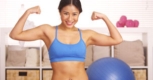 Strong Japanese woman showing off muscles Stock Photo