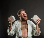 Strong karateka breaks a brick. Over grey royalty free stock photos