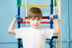 Strong kid boy exercising with dumbbells Stock Photo