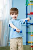 Strong kid exercising with dumbbells. Strong kid boy exercising with dumbbells. Healthy life, sportive child Stock Image