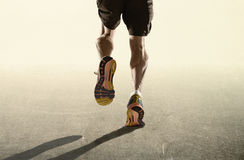 Strong legs and running shoes of sport man jogging in fitness healthy endurance concept in advertising style. Rear view close up strong athletic legs and running royalty free stock image