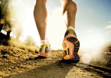 Strong legs and shoes of sport man jogging in fitness training workout on off road. Close up feet with running shoes and strong athletic legs of sport man stock photography
