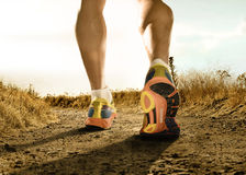 Strong legs and shoes of sport man jogging in fitness training workout on off road Stock Photos