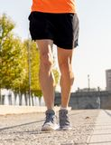 Strong legs of young runner running jogging in city street at sunset in city training workout stock photography