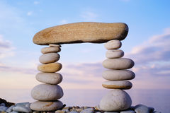Strong Link. Long horizontal stone is between a pebble piles Stock Images