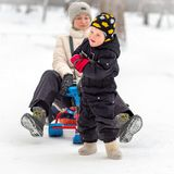 Strong little boy carries her mother on a sled royalty free stock photography
