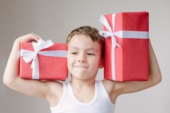 Strong little boy in t-shirt holding two boxes of gifts on his s royalty free stock image