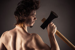 Strong lumberjack back with an ax in hand Stock Images