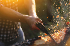 Strong lumberjack chopping wood. Chips fly apart Stock Photo