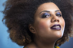 Strong make up african american woman looking down. Young black female with vivid make-up, blue background, nicely toned skin Royalty Free Stock Photo