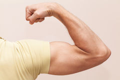 Strong male arm shows biceps Royalty Free Stock Image