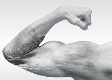 Strong male arm shows biceps with coastal sea landscape Royalty Free Stock Images