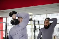 Strong male athlete raising dumbbells, looking at workout results in the mirror. Stock footage Royalty Free Stock Photo