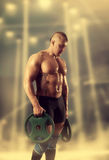 Strong male bodybuilder with pancakes from barbell Royalty Free Stock Photo