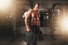 Strong male bodybuilder with pancakes from barbell. Exercise with barbell in sport gym. Fitness training with weight. Bodybuilding workout stock images