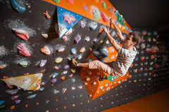 Strong male climber on boulder climbing wall indoor Stock Photo