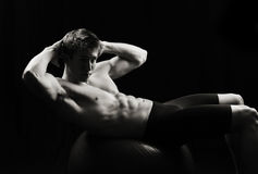 Strong male doing situps on a balance ball Royalty Free Stock Images