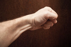 Strong male fist over dark brown wooden wall Stock Photos