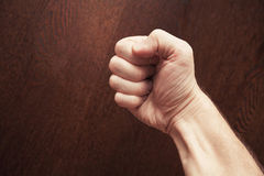 Strong male fist over dark wooden background Royalty Free Stock Photo
