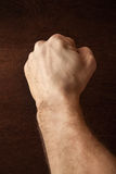 Strong male fist over dark wooden wall. Background Royalty Free Stock Photography