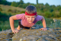 Strong Male Kid Doing Push up on Big Rock Stock Photos