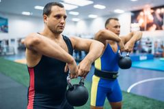 Strong male lifters doing exercise with kettlebell royalty free stock images