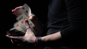 Slow-motion shooting, man in black jacket shows focus with playing cards. Strong male magician in black jacket shows focus with cards stock video footage