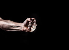 Strong male man raised fist on a black background, power, war, p Royalty Free Stock Photos