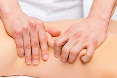 Strong male masseur`s hands knead the skin and muscles. Of the back Royalty Free Stock Image