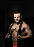 Strong male  poses holding steel chain Stock Images