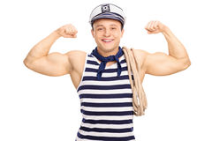 Strong male sailor flexing his biceps. Strong male sailor carrying a rope and flexing his biceps isolated on white background Royalty Free Stock Image