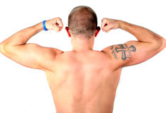Strong Man. A young tatooed man is flexing his muscles on his arms and his back. Tatoo says - only the strong survive! Isolated over white Royalty Free Stock Photo