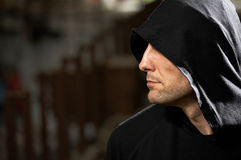 Strong man. Profile of the man in a hood on a black background Stock Photo