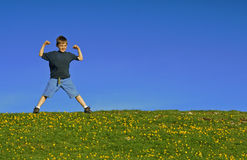Strong Man. Young boy flexing his muscles on a hill against a blue sky Stock Photo