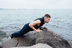 Strong man acts yoga on the rocks beach in the morning against sea. Stock Photos