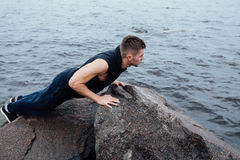 Strong man acts yoga on the rocks beach in the morning against sea. Royalty Free Stock Photos