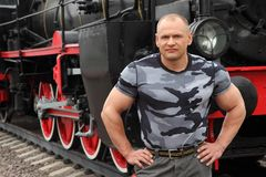 Strong man against locomotive Royalty Free Stock Photos