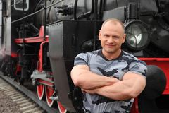 Strong man against locomotive Stock Photography