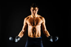 Strong man with black boxing gloves. Strong determined fit man with toned body Royalty Free Stock Images