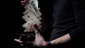 Male magician shows tricks with cards on a black background. Strong man in black jacket shows focus with playing cards stock video footage