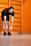 Strong man in the black sportwear stretching arms before gym workout against bright orange wall. Stock Image