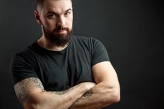 Strong man in black tight fitted shirt with a serious expression on his face. Portrait of a handsome beared strong man with muscular tattooed hands keeping stock images